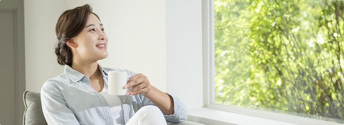 잔을 들고 창밖을 보는 여성